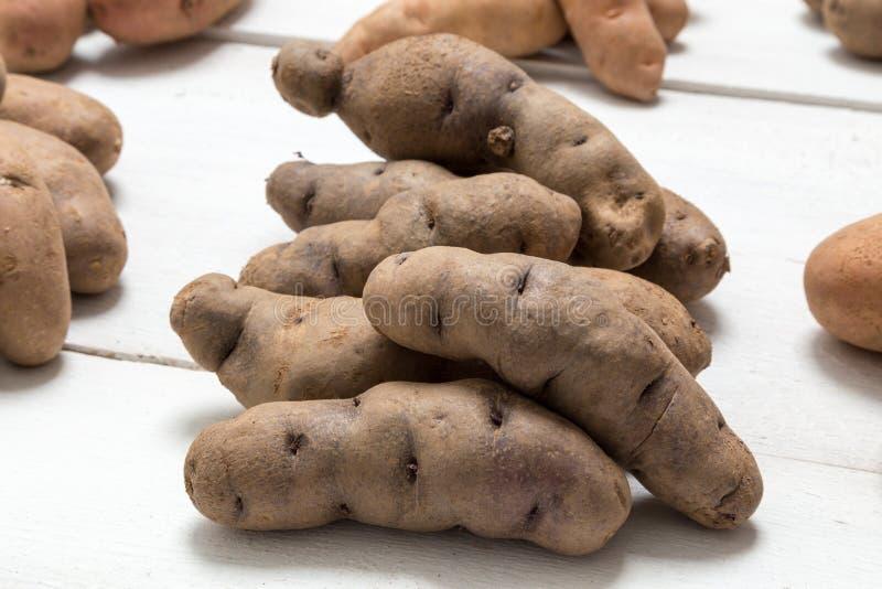 Aardappels op wit houten raadsconcept stock afbeeldingen