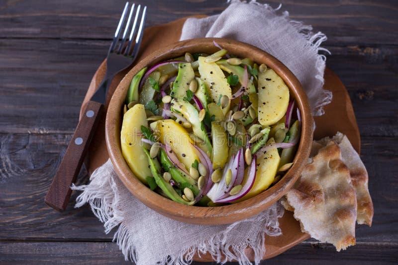 Aardappelsalade met groenten in het zuur, avocado, rode ui en pompoenzaden stock fotografie