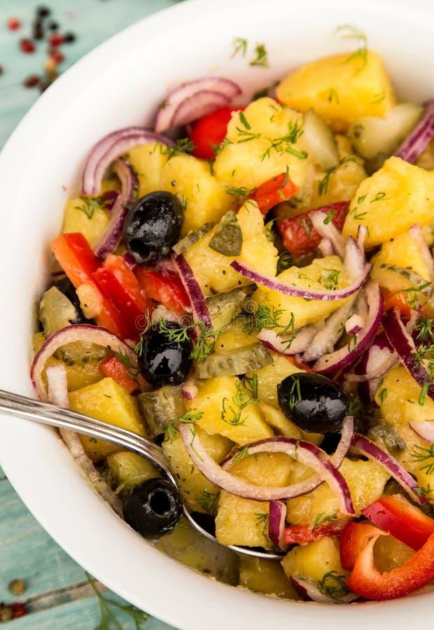 Aardappelsalade met ui, olijven, peper, ingelegde komkommer en dille stock afbeeldingen