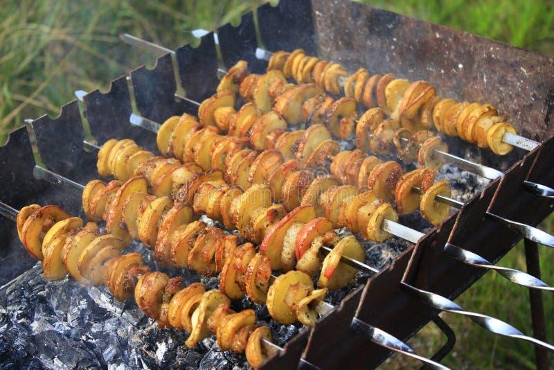 Aardappelvleespennen met bacon Het gemarineerde shashlik voorbereidingen treffen bij de barbecuegrill over houtskool royalty-vrije stock foto