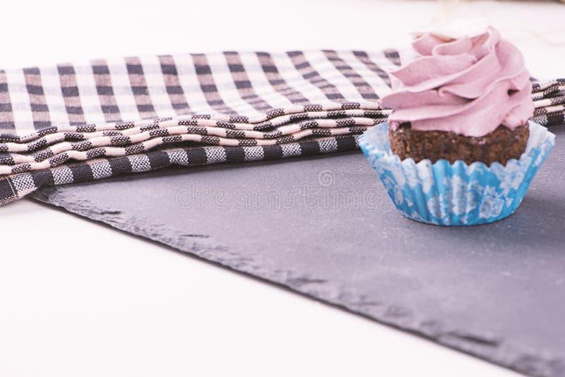 Aardbei cupcake met een servet op zwarte basis stock foto