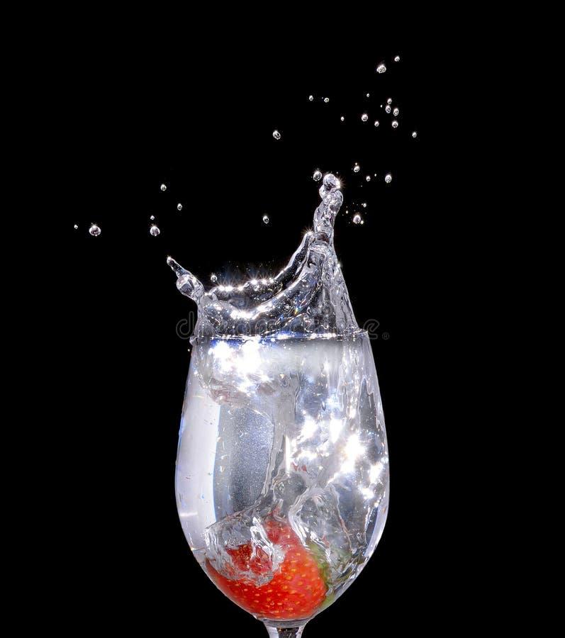Aardbei een glas water met een nevel van waterdruppeltjes in mo stock foto