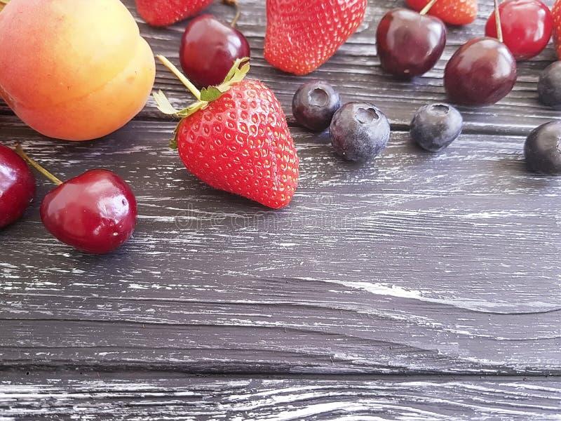 Aardbei, kers, bosbes, heerlijke abrikoos op een houten achtergrond royalty-vrije stock afbeelding
