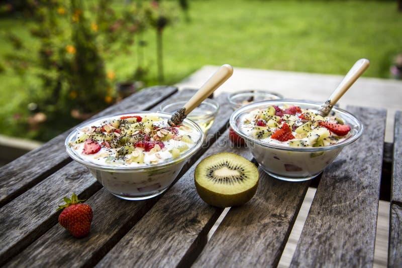 Aardbei-kiwi-yoghurt met granola, chia-zaden en agave-stroop in glaskommen royalty-vrije stock afbeeldingen