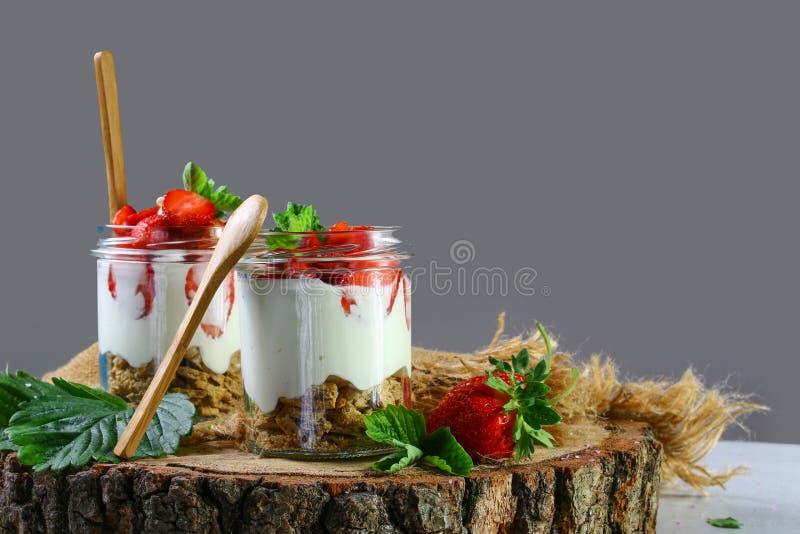Aardbei met slagroom in een glas Gastronomisch dessert met verse de zomerbessen en weelderige room, op een houten stomp, selectie stock foto