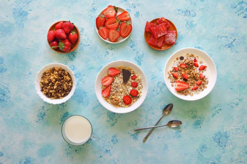 Aardbei, muesli, melk en Turkse verrukking op een turkooise lijst stock foto