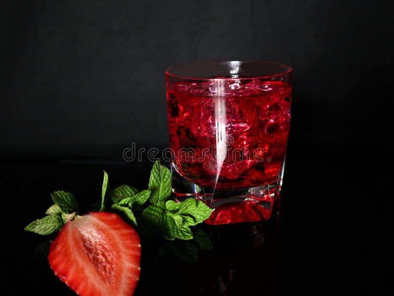Aardbei, munt, ijs, drank op een zwarte achtergrond stock foto's