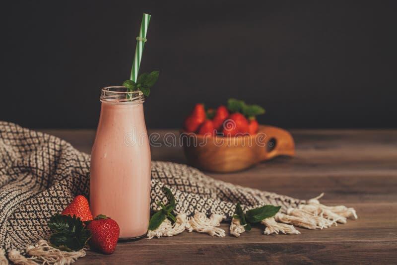 Aardbei smoothie of milkshake in kruik met verse aardbeien in houten kom op rustieke achtergrond royalty-vrije stock foto