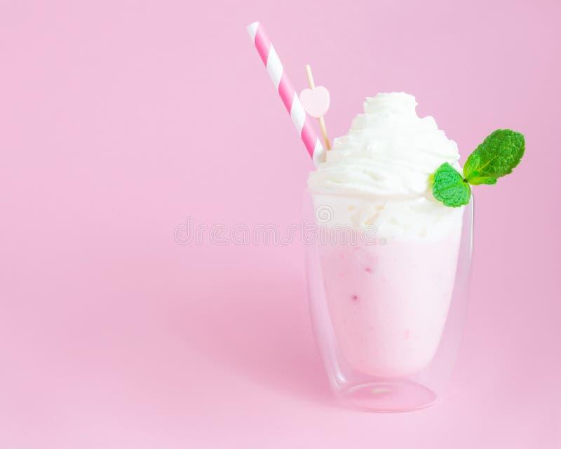Aardbei smoothie of milkshake met slagroom en muntbladeren op roze achtergrond Gezond voedsel voor ontbijt en snack stock foto