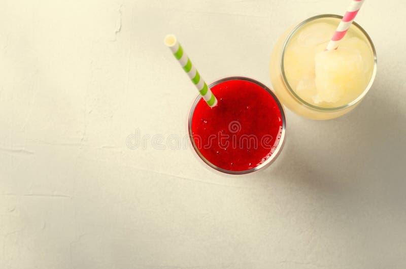 Aardbei smoothies en ijslimonade met cocktailbuizen in glazen, op witte achtergrond royalty-vrije stock foto