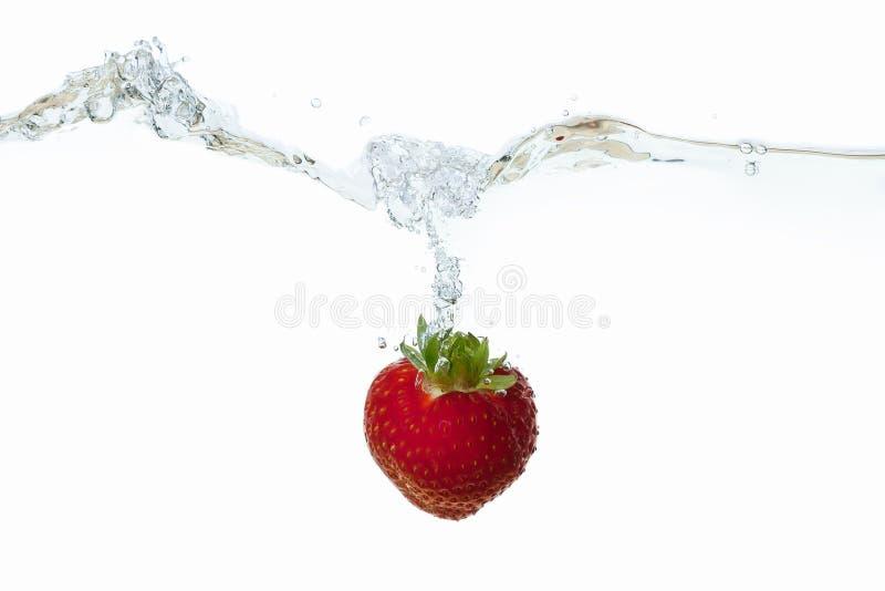 Aardbei in waterplons wordt gelaten vallen op wit dat stock afbeelding