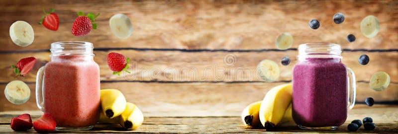 Aardbeibanaan en bosbessenbanaan smoothies stock afbeelding
