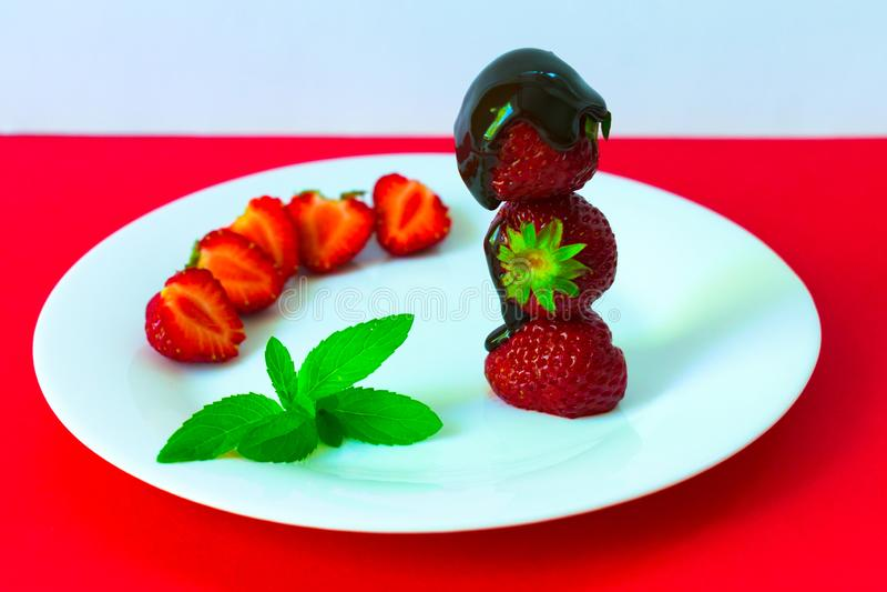 Aardbeien in chocolade en munt op een witte plaat Rode achtergrond royalty-vrije stock fotografie
