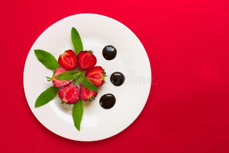 Aardbeien in chocolade en muntbladeren op een plaat Rode achtergrond, mening vanaf de bovenkant royalty-vrije stock foto