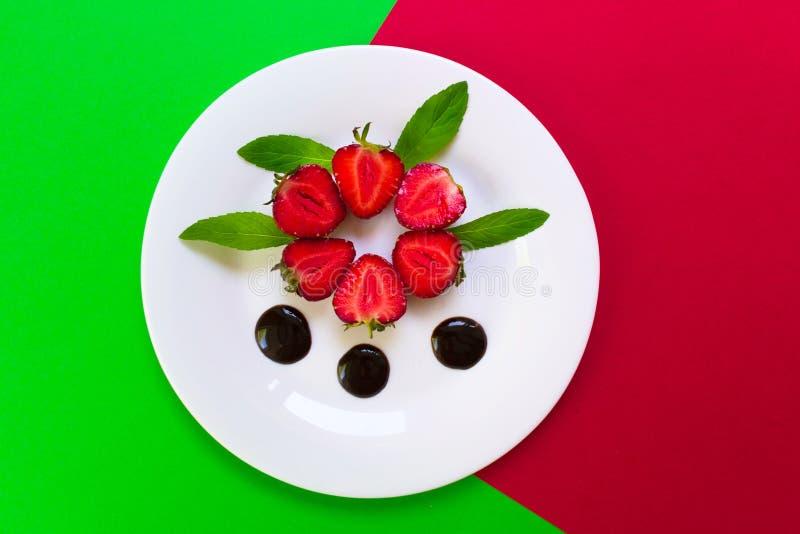 Aardbeien in chocolade en muntbladeren Rode en groene achtergrond royalty-vrije stock afbeeldingen