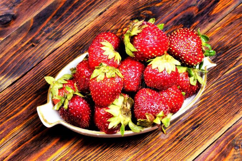 Aardbeien - de bessen zijn helder rood op een houten achtergrond De tuin van de aardbeibes, gezond voedsel, zoet dessert, populai stock afbeelding