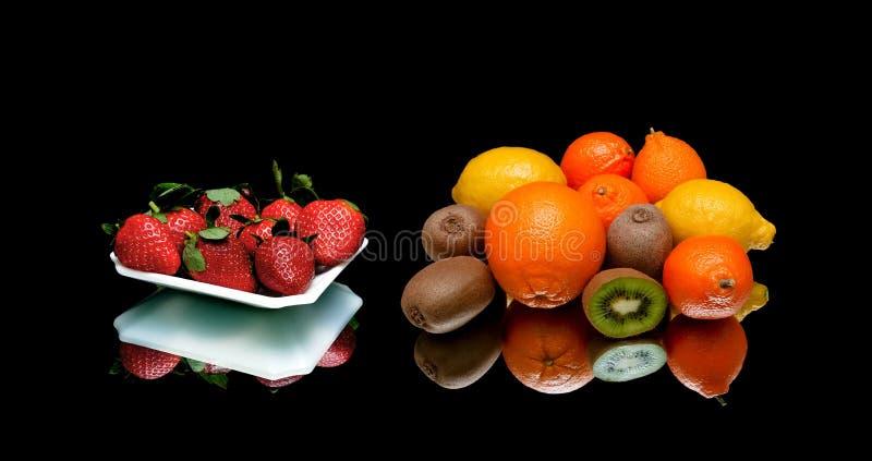 Aardbeien en andere vruchten op een zwarte achtergrond stock fotografie