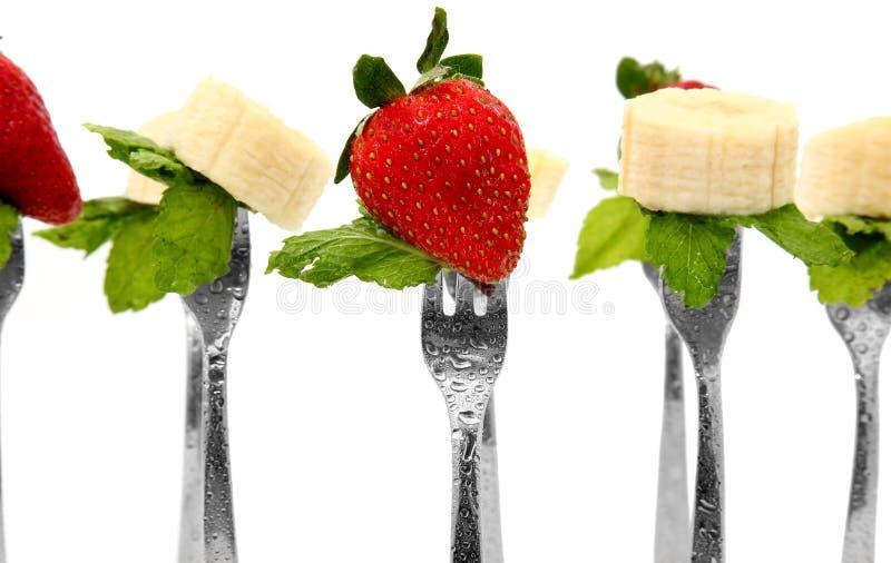 Aardbeien en Bananen met munt op Vorken stock fotografie