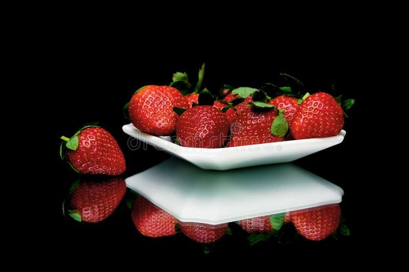 Aardbeien op een plaat op een zwarte achtergrond met spiegel reflec stock afbeeldingen