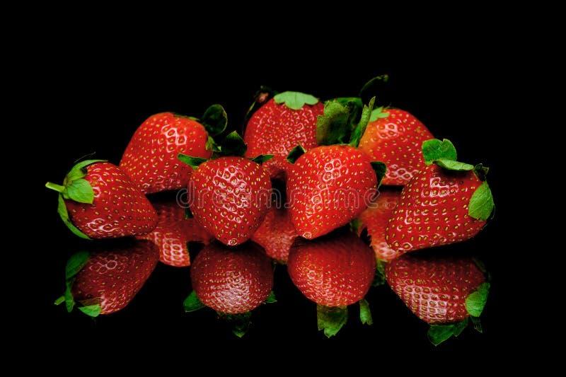 Aardbeien op een zwarte achtergrond met spiegelbezinning stock afbeeldingen