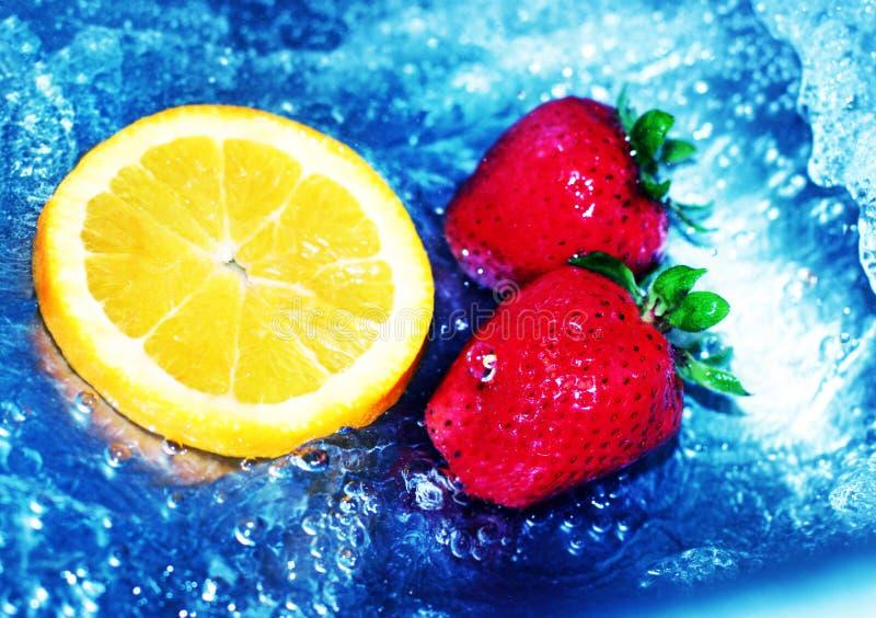 Aardbeien, oranje plak, en water royalty-vrije stock foto