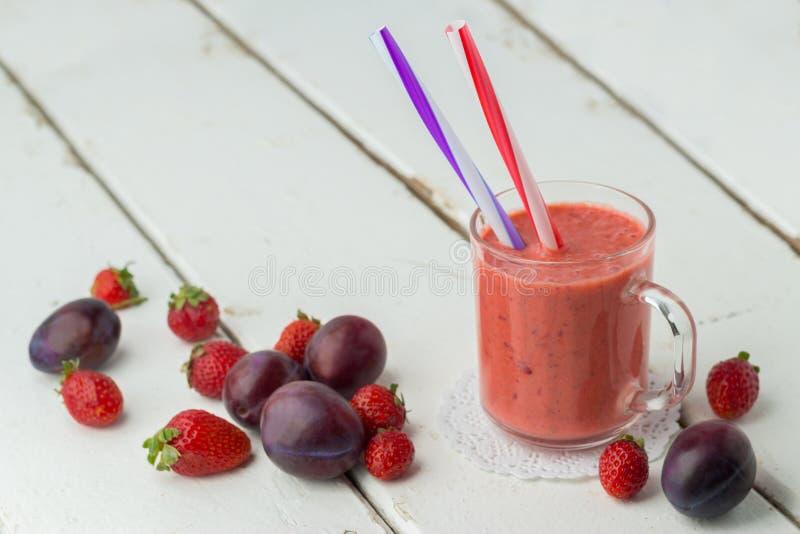Aardbeipruim smoothie in een glas met een stro royalty-vrije stock afbeeldingen