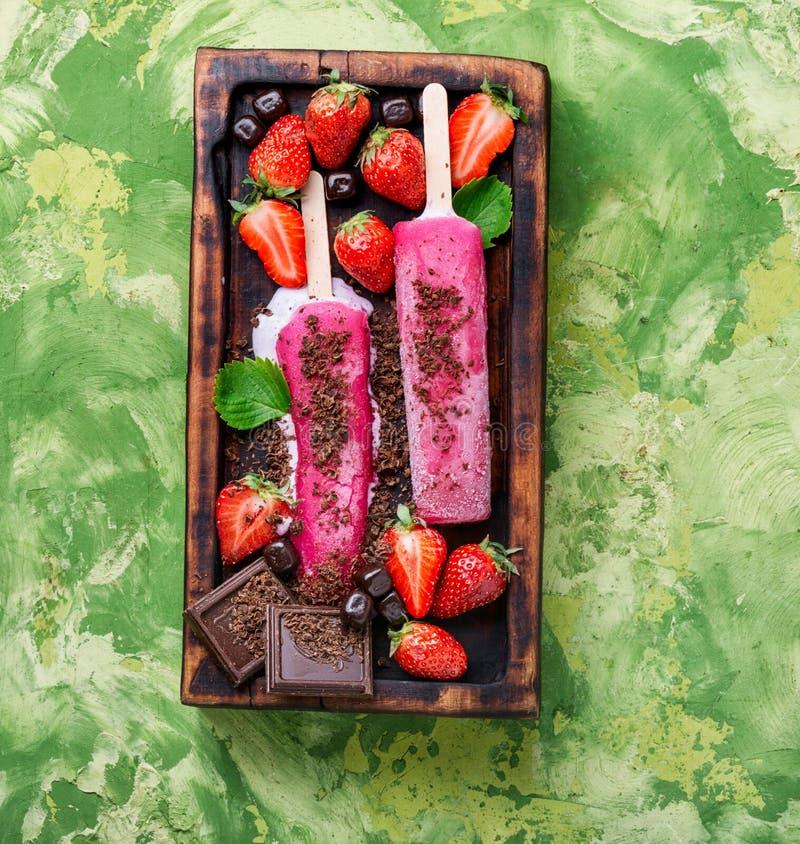 Aardbeiroomijs of ijslollys stock fotografie