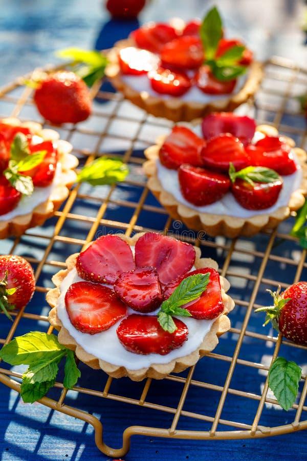 Aardbeitaartjes, kleine shortcrusttaartjes met de toevoeging van roomkaas, verse aardbeien en munt bij het koelen van dienblad op stock foto