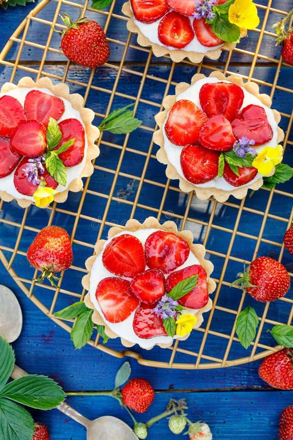 Aardbeitaartjes, kleine zandkoektaartjes met de toevoeging van roomkaas, verse aardbeien en munt bij het koelen van dienblad royalty-vrije stock foto