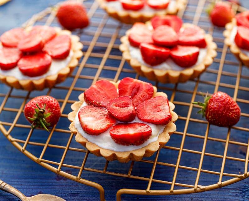 Aardbeitaartjes, kleine zandkoektaartjes met de toevoeging van roomkaas, verse aardbeien op een koeldienblad royalty-vrije stock foto