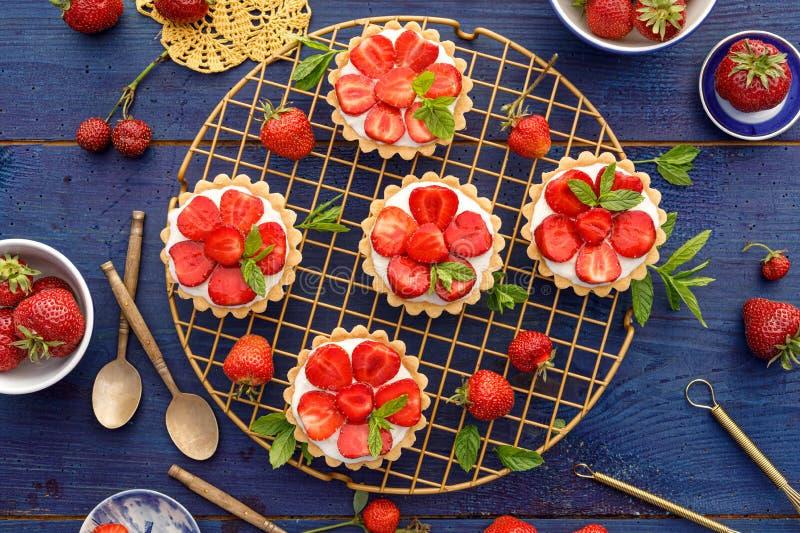 Aardbeitaartjes, kleine zandkoektaartjes met de toevoeging van roomkaas, verse aardbeien op een koeldienblad royalty-vrije stock afbeelding