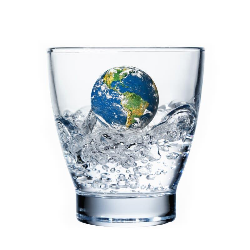 Aarde die in een glas water verdrinkt stock afbeelding
