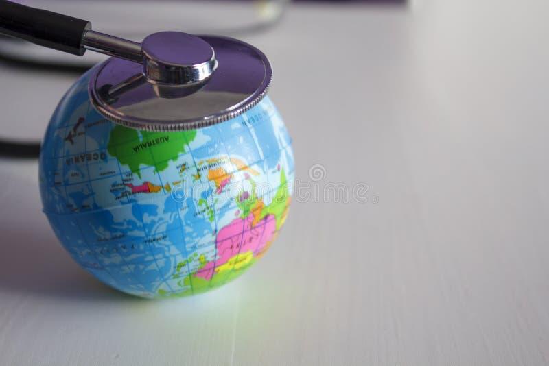 Aarde en stethoscoop globaal gezondheidszorgconcept stock foto's