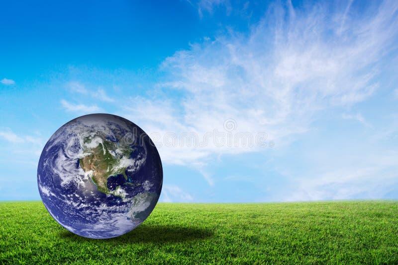 Aarde mooi op groen gras met wolkenhemel, wereld met behoud stock fotografie