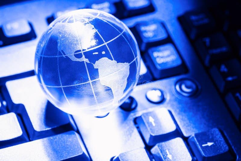 Aarde van de wereld de transparante bol op computertoetsenbord Globaal communicatie bedrijfsconcept Gestemd blauw stock afbeelding