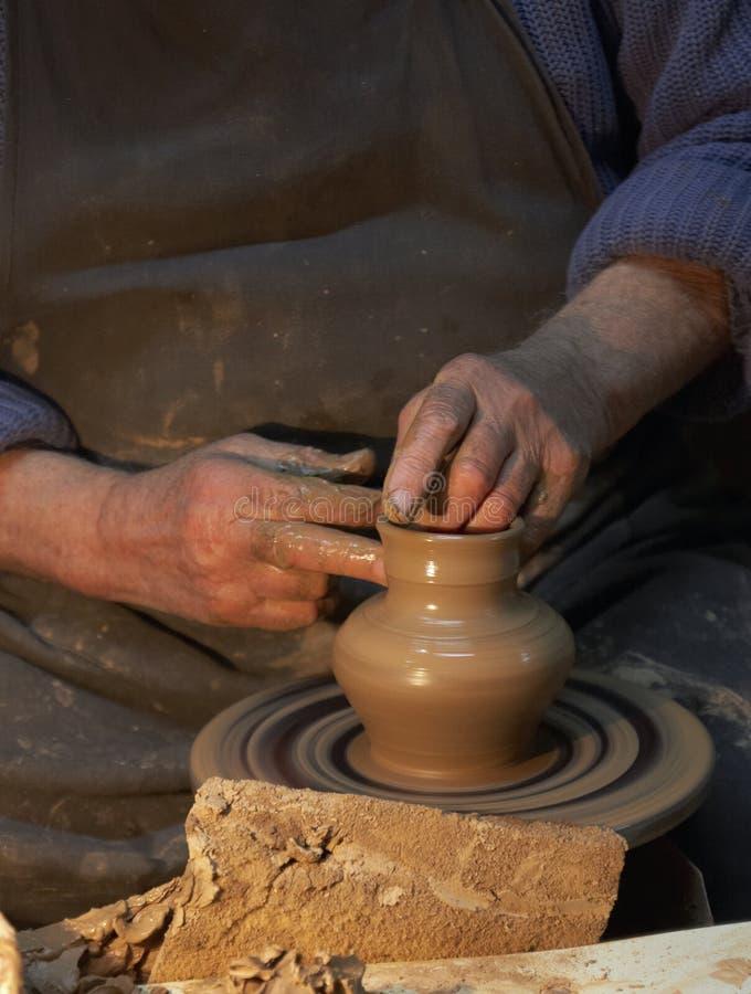 Aardewerk Handen van een pottenbakker die een kruik klei maakt ambacht stock foto