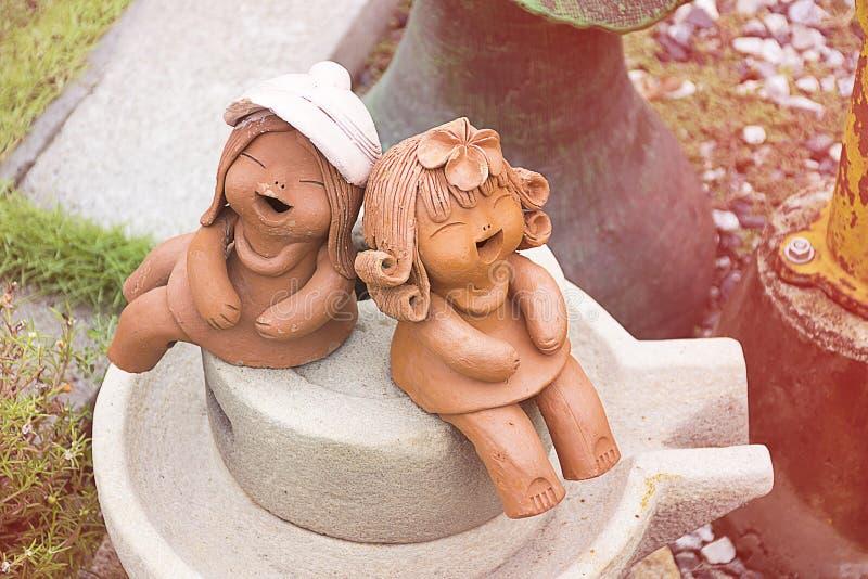 Aardewerk of keramiek de glimlach van de jong geitjepop/lach en zitting stock fotografie