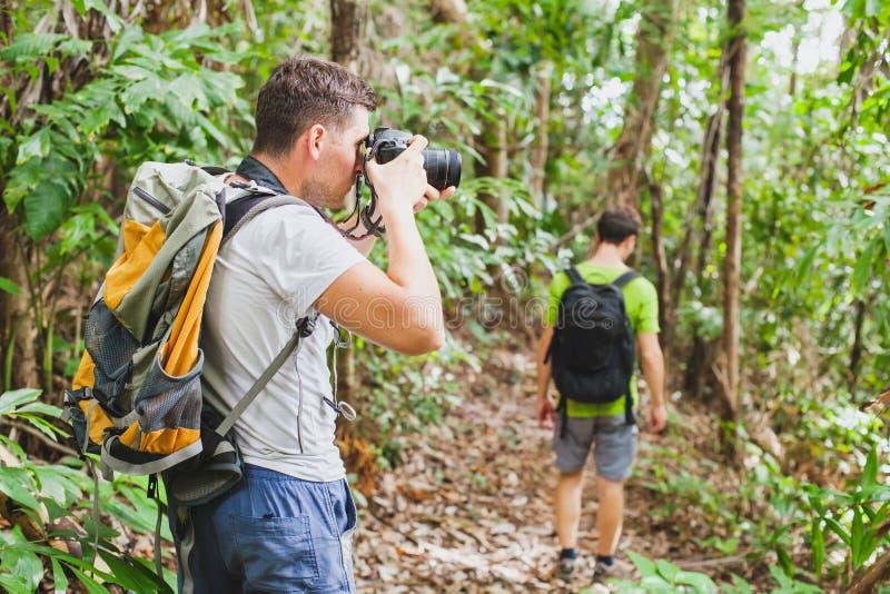Aardfotograaf in tropische wildernis, groep toeristen die in het bos wandelen stock fotografie