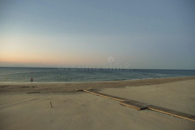 aardig beeld van een leeg strand bij zonsondergang stock afbeelding