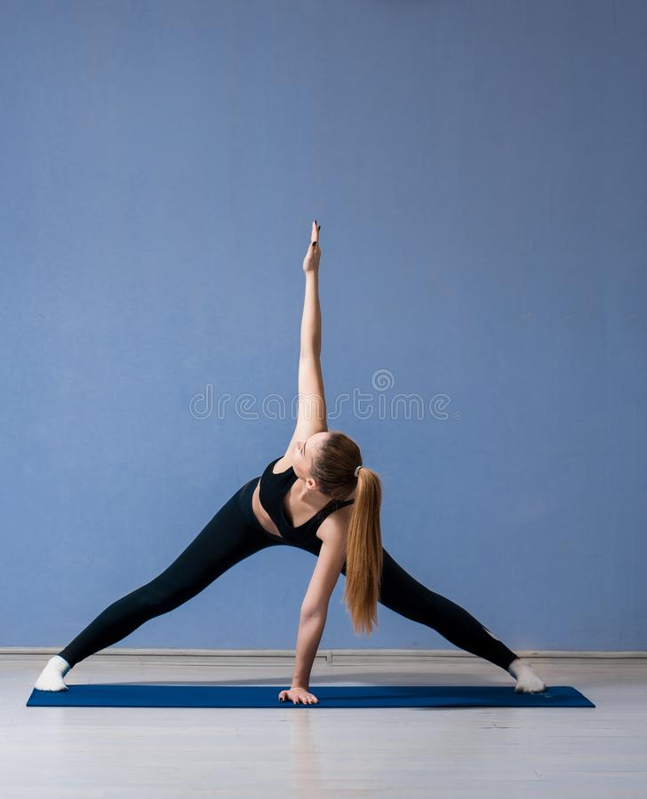 aardig meisje in een aangestoken yogaruimte die oefeningen doen royalty-vrije stock afbeelding