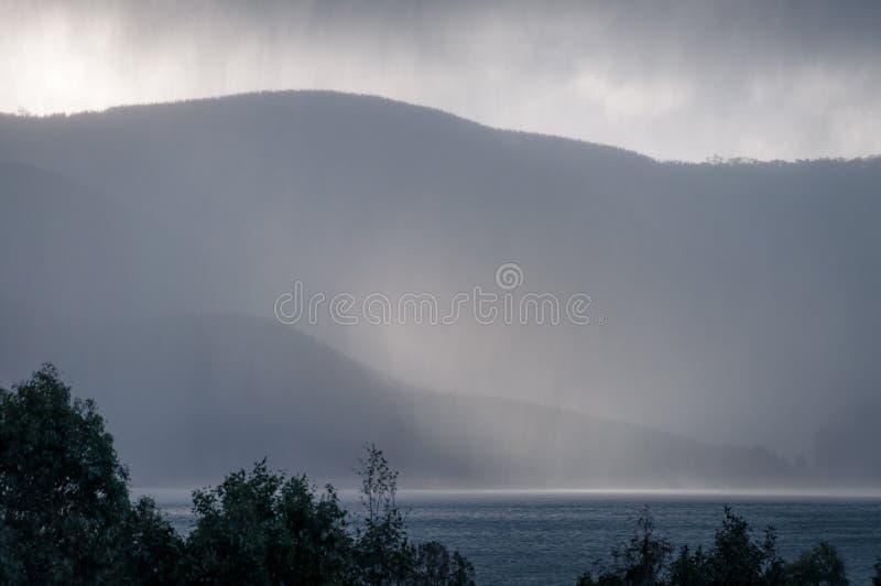 Aardlandschap met silhouetten van bergen en zware regenstortbui royalty-vrije stock afbeelding