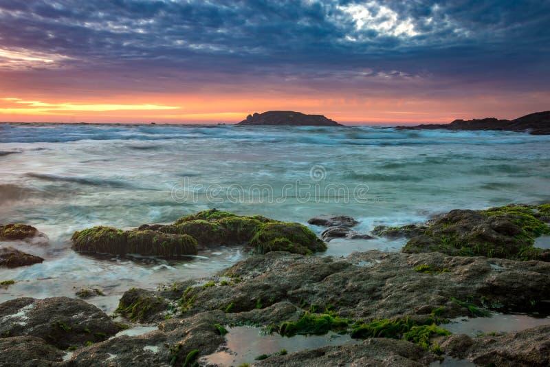 Aardzeegezicht met Groen Moss Covered Rocks, Vage Golven, Eiland en Kleurrijke Wolken bij Zonsopgang royalty-vrije stock fotografie