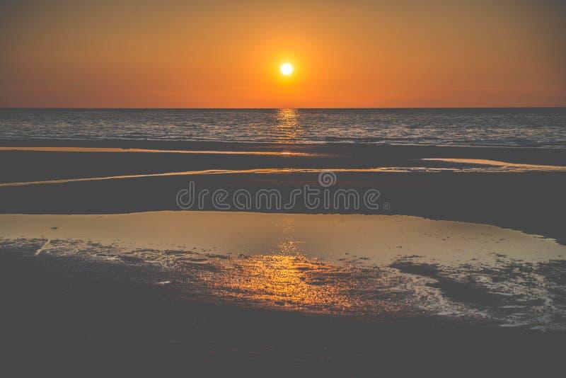 Aardzonsondergang bij kust stock afbeelding