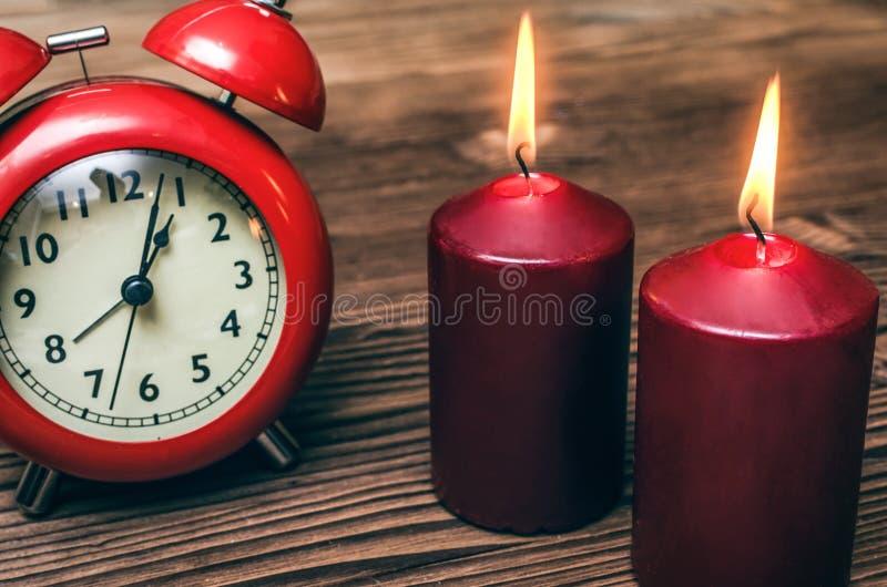 Aarm-Uhr und brennende Kerze lizenzfreie stockfotografie