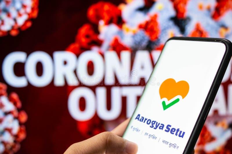Aarogya Setu App angemeldet auf einem Mobiltelefon vor einem roten Bildschirm mit Coronavirus geschrieben lizenzfreies stockfoto