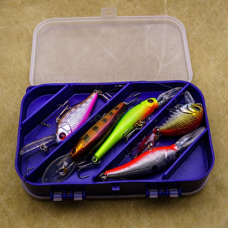 Aas voor visserij op canvasachtergrond Verscheidene wobblers van verschillende kleuren in de doos voor vistuig stock foto