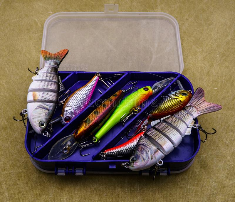 Aas voor visserij op canvasachtergrond Verscheidene wobblers van verschillende kleuren in de doos voor vistuig stock afbeeldingen