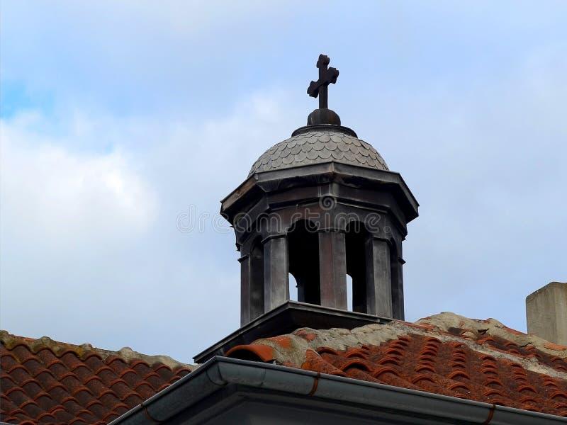 A abóbada de uma capela velha com uma cruz sobre os telhados telhados contra o céu foto de stock royalty free