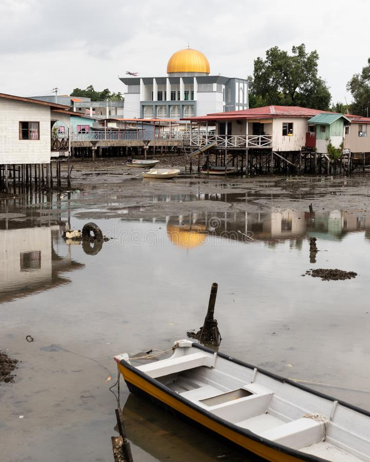 Abóbada dourada da mesquita acima da ruína pobre da vila da pobreza corrida para baixo foto de stock