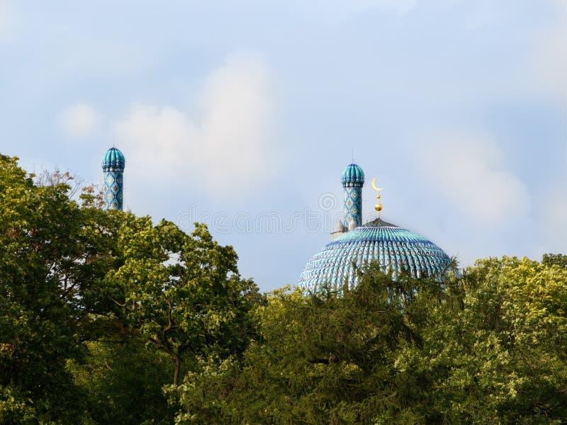 Abóbada e minarete principais da mesquita de St Petersburg atrás das árvores em um céu azul do fundo foto de stock